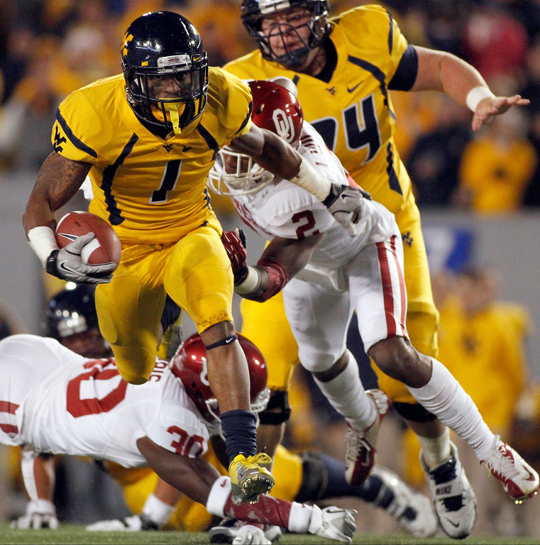 . Tavon Austin #1 of the West Virginia Mountaineers carries the ball against Julian Wilson #2 of the Oklahoma Sooners during the game on November 17, 2012 at Mountaineer Field in Morgantown, West Virginia.  (Photo by Justin K. Aller/Getty Images)