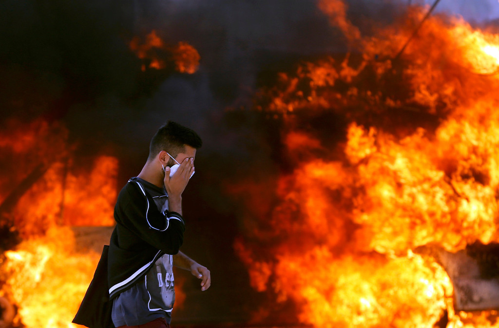 . A protester wipes his eyes as he passes next to a burning vehicle during a protest at Taksim Square in Istanbul June 11, 2013.   REUTERS/Murad Sezer
