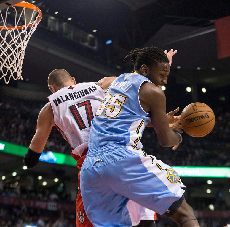 . Denver Nuggets\' Kenneth Faried, right, battles for a rebound with Toronto Raptors\' Jonas Valanciunas during the first half of an NBA basketball game on Sunday, Dec. 1, 2013, in Toronto. (AP Photo/The Canadian Press, Chris Young)