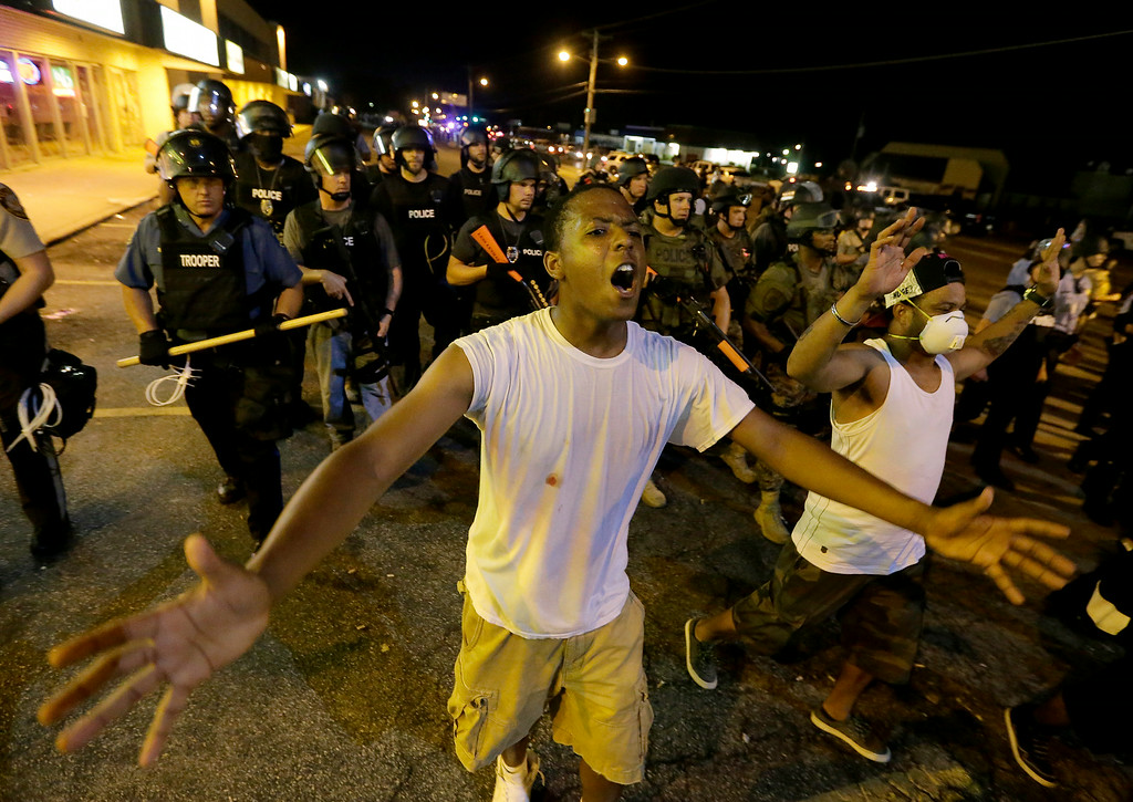 . People are moved peacefully by a line of police as authorities disperse a protest in Ferguson, Mo. early Wednesday, Aug. 20, 2014. On Saturday, Aug. 9, 2014, a white police officer fatally shot Michael Brown, an unarmed black teenager, in the St. Louis suburb. (AP Photo/Charlie Riedel)