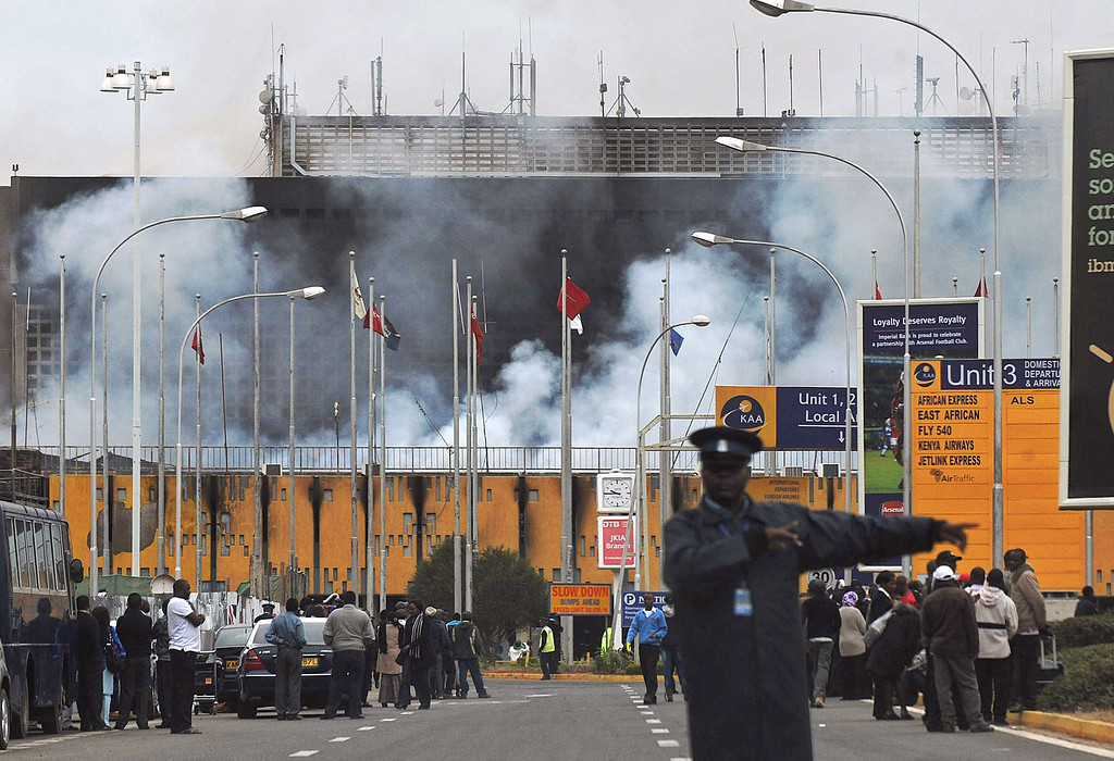 . A police officer directs traffic away as smokes billows from the Jomo Kenyatta International airport in Nairobi on August 7, 2013.   AFP PHOTO / Tony  KARUMBA/AFP/Getty Images