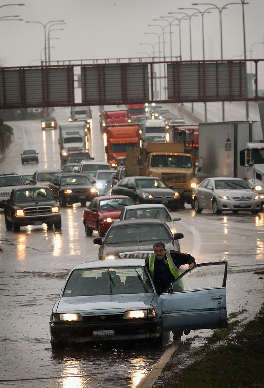 . A motorist pushes his disabled car after it died while driving through a flooded section of the Kennedy Expressway on April 18, 2013 in Chicago, Illinois. Thunderstorms dumped up to 5 inches of rain on parts of the Chicago area overnight, closing sections the Edens, Eisenhower and Kennedy expressways, which lead to and from downtown, during the morning rush.  (Photo by Scott Olson/Getty Images)
