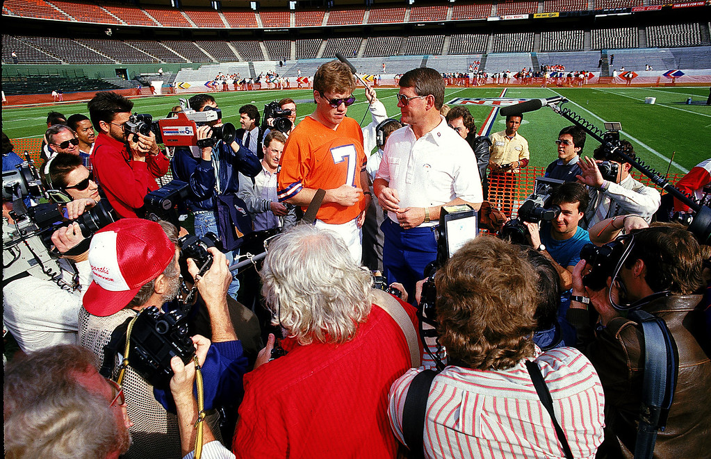 . John Elway #7 of the Denver Broncos and Dan Reeves talk to the press before Super Bowl XXII against the Washington Redskins at the Jack Murphy Stadium in San Diego, California. The Redskins defeated the Broncos 42-10.