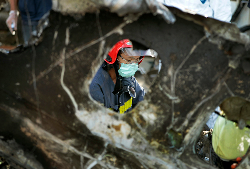 . A forensic team recovers human remains at the wreckage scene of crashed TransAsia Airways Flight GE222 on the outlying island of Penghu, Taiwan, Thursday, July 24, 2014.  (AP Photo/Wally Santana)