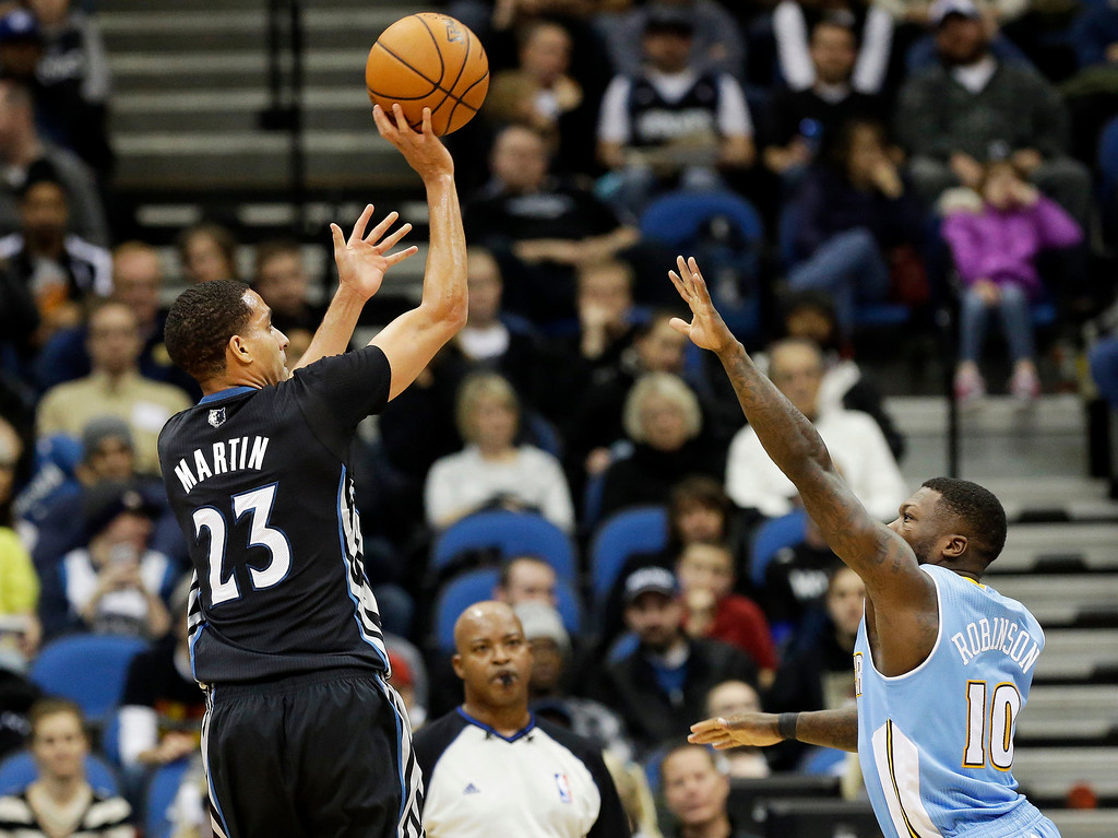 . Minnesota Timberwolves\' Kevin Martin,left, shoots over Denver Nuggets\' Nate Robinson in the second half of an NBA basketball game on Wednesday, Nov. 27, 2013, in Minneapolis. The Nuggets won 117-110. Martin led the Timberwolves with 29 points. (AP Photo/Jim Mone)