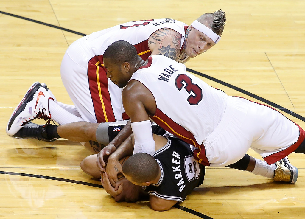 . Miami Heat\'s Dwyane Wade (3) and Chris Andersen scramble for the ball with San Antonio Spurs\' Tony Parker during the fourth quarter in Game 7 of their NBA Finals basketball playoff in Miami, Florida June 20, 2013. REUTERS/Joe Skipper