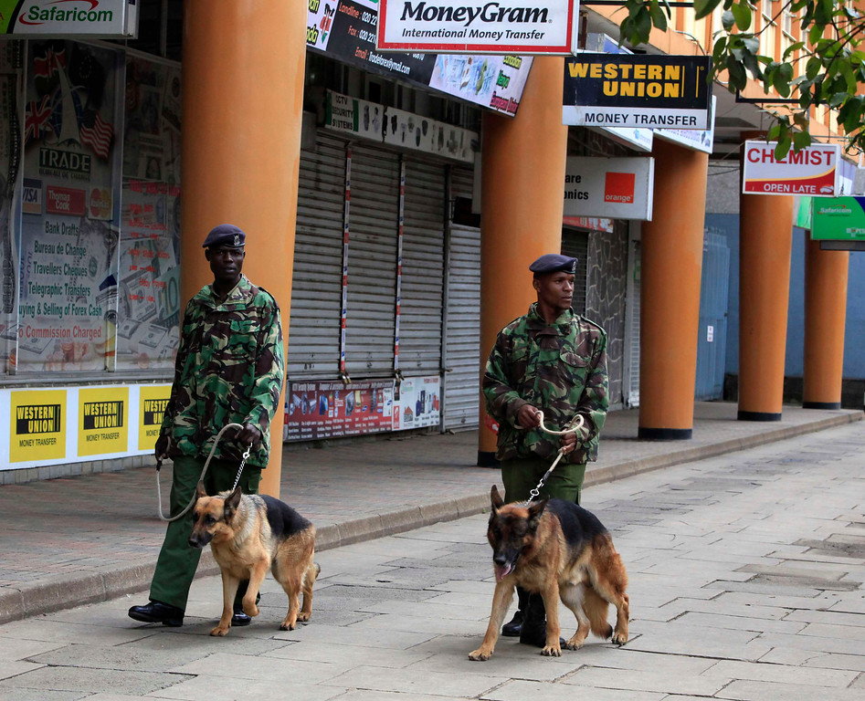 . Kenyan policemen with dogs patrol the street near the Supreme Court in capital Nairobi March 30, 2013. Kenya\'s Supreme Court said on Saturday it would issue its ruling no later than 1400 GMT on legal challenges to Uhuru Kenyatta\'s win in a presidential election seen as a test of democracy, five years after vote disputes triggered widespread bloodshed. REUTERS/Noor Khamis