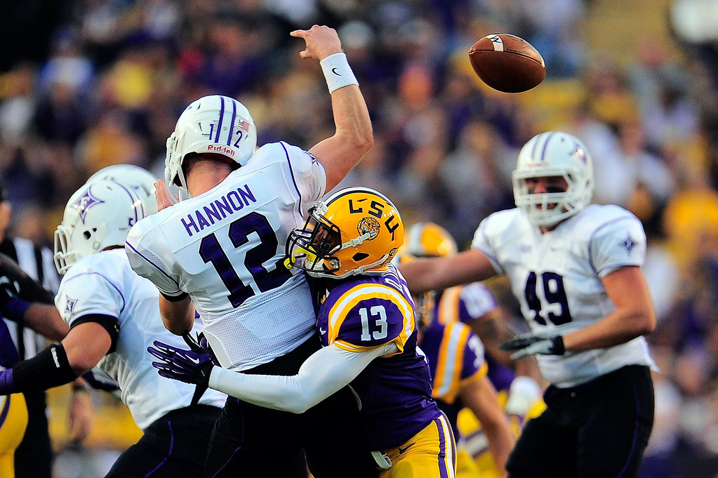 . BATON ROUGE, LA - OCTOBER 26:  Reese Hannon #12 of the Furman Paladins loses the ball after being hit by Dwayne Thomas #13 of the LSU Tigers during a game at Tiger Stadium on October 26, 2013 in Baton Rouge, Louisiana.  (Photo by Stacy Revere/Getty Images)
