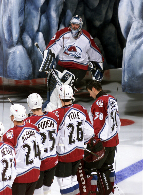 . Patrick Roy emerges from out the Mountain that hangs in front of the bench during introductions as other team members look on. It was the first night the Avalanche had played in the newly built Pepsi Center as they took on the Boston Bruins. (John Leyba/The Denver Post)
