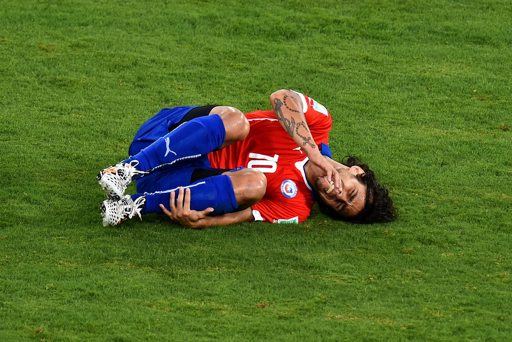 . Jorge Valdivia of Chile lies on the field after a foul during the 2014 FIFA World Cup Brazil Group B match between Chile and Australia at Arena Pantanal on June 13, 2014 in Cuiaba, Brazil.  (Photo by Stu Forster/Getty Images)