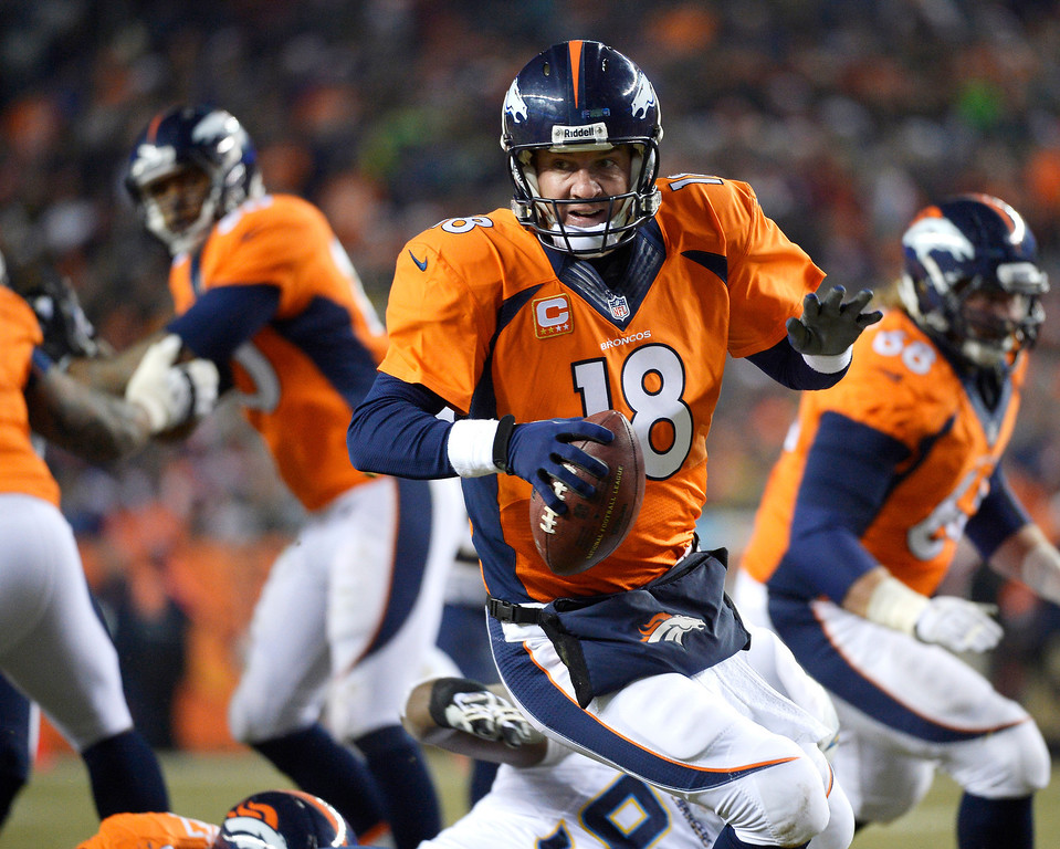 . Denver Broncos quarterback Peyton Manning (18) scrambles during the second quarter against the San Diego Chargers on Dec. 12, 2013.   (Photo by Joe Amon/The Denver Post)