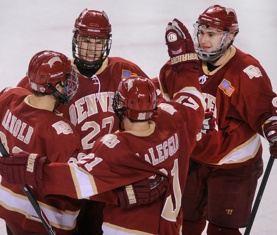 . DENVER, CO. - OCTOBER 25: Denver center Quentin Shore (27) celebrated a goal with teammates Gabe Levin (9) Joey LaLeggia (21) and Grant Arnold (39) in the second period. The University of Denver hockey team hosted Niagara at Magness Arena Friday night, October 25, 2013. Photo By Karl Gehring/The Denver Post