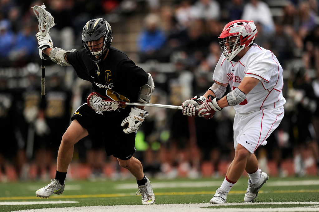 . DENVER, CO - MAY 15: Arapahoe High School senior midfielder Ben Eigner #8, left, carries the ball while defended by Regis Jesuit freshman defenseman Ian Desmond #15 during a CHSAA 5A boys lacrosse semifinal game on May 15, 2013, in Denver, Colorado. Arapahoe won 13-5 to advance to the finals. (Photo by Daniel Petty/The Denver Post)