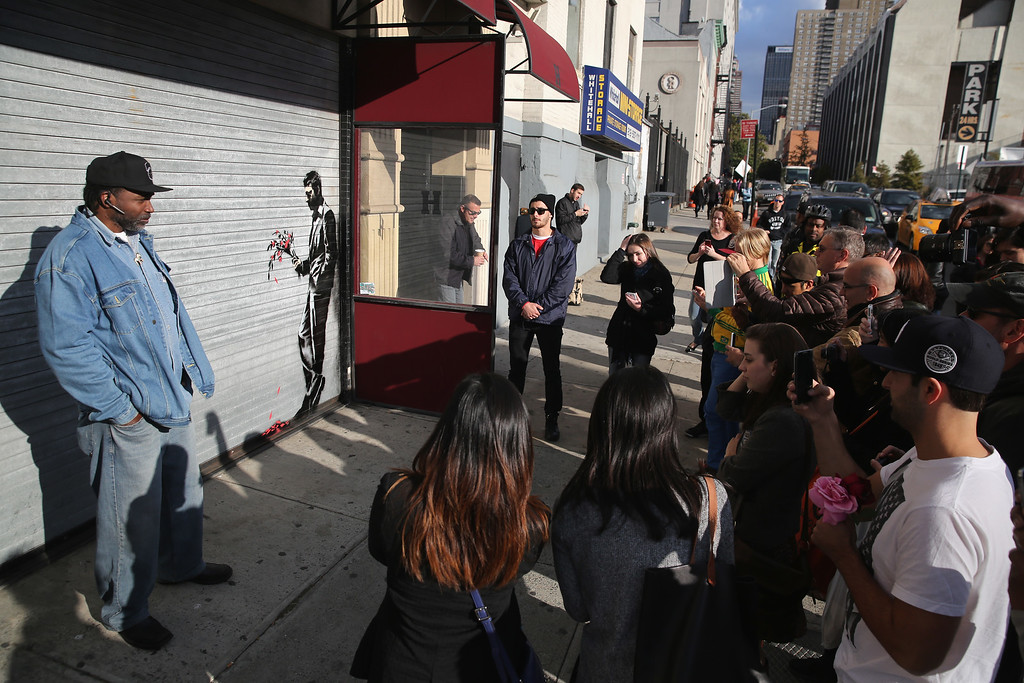 ". NEW YORK, NY - OCTOBER 24:  A crowd of people gather to see a painting by British street artist Banksy on a roll-down security gate covering the main entrance to Larry Flint\'s Hustler Club on October 24, 2013 in the Hell\'s Kitchen neighborhood of New York City. On Banksy\'s website a caption for the work reads, ""Waiting in vain...at the door of the club.\""  (Photo by John Moore/Getty Images)"