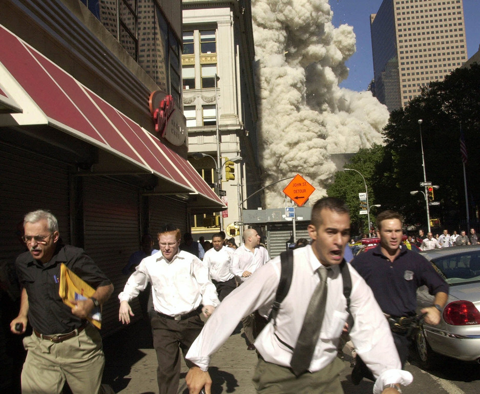 . People run from the collapse of World Trade Center Tower  Tuesday, Sept. 11, 2001 in New York.  Charlie Ross is seen fourth from the left.  (AP Photo/Suzanne Plunkett)
