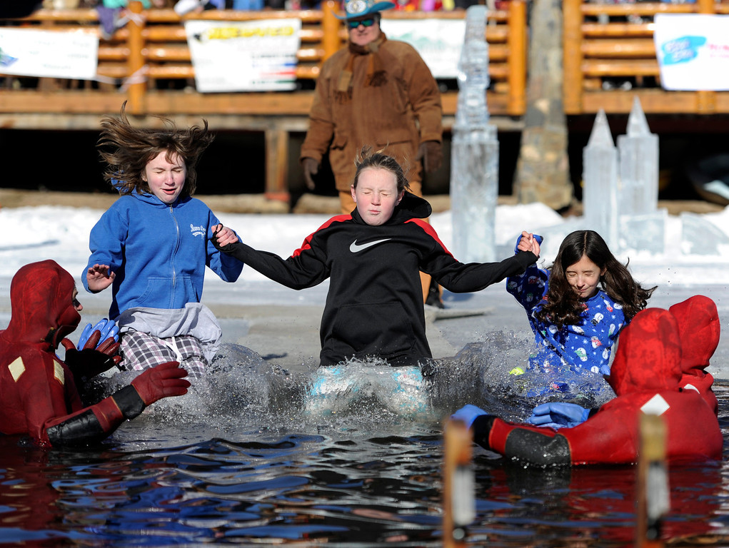 . Dozens joined in for the 6th annual Evergreen Lake Plunge on New Years Day, 2013, where only the very brave jumped, dove, and even performed a belly flop into the icy waters of Evergreen Lake. Friends from left to right Mollie Markey, Marla Hadsell, and Caroline Petterson take the plunge as a unified trio.Kathryn Scott Osler, The Denver Post