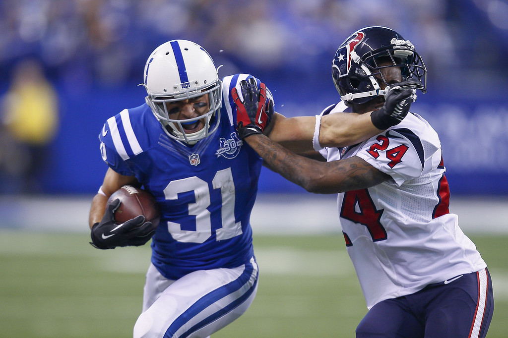 . Donald Brown #31 of the Indianapolis Colts runs the brown and give a stiff arm to Johnathan Joseph #24 of the Houston Texans at Lucas Oil Stadium on December 15, 2013 in Indianapolis, Indiana. (Photo by Michael Hickey/Getty Images)