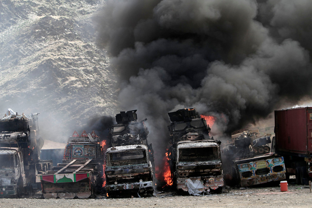 . Smoke rises from  NATO supply trucks following an attack by militants in the Torkham area near the Pakistan-Afghanistan border in the Jalalabad province east of Kabul, Afghanistan, Monday, Sept 2, 2013. The Taliban claimed responsibility for the strike on a U.S. base in Afghanistan near the border with Pakistan on Monday, setting off bombs, torching vehicles and shutting down a key road used by NATO supply trucks, officials said. Several people were killed.   (AP Photo/Rahmat Gul)