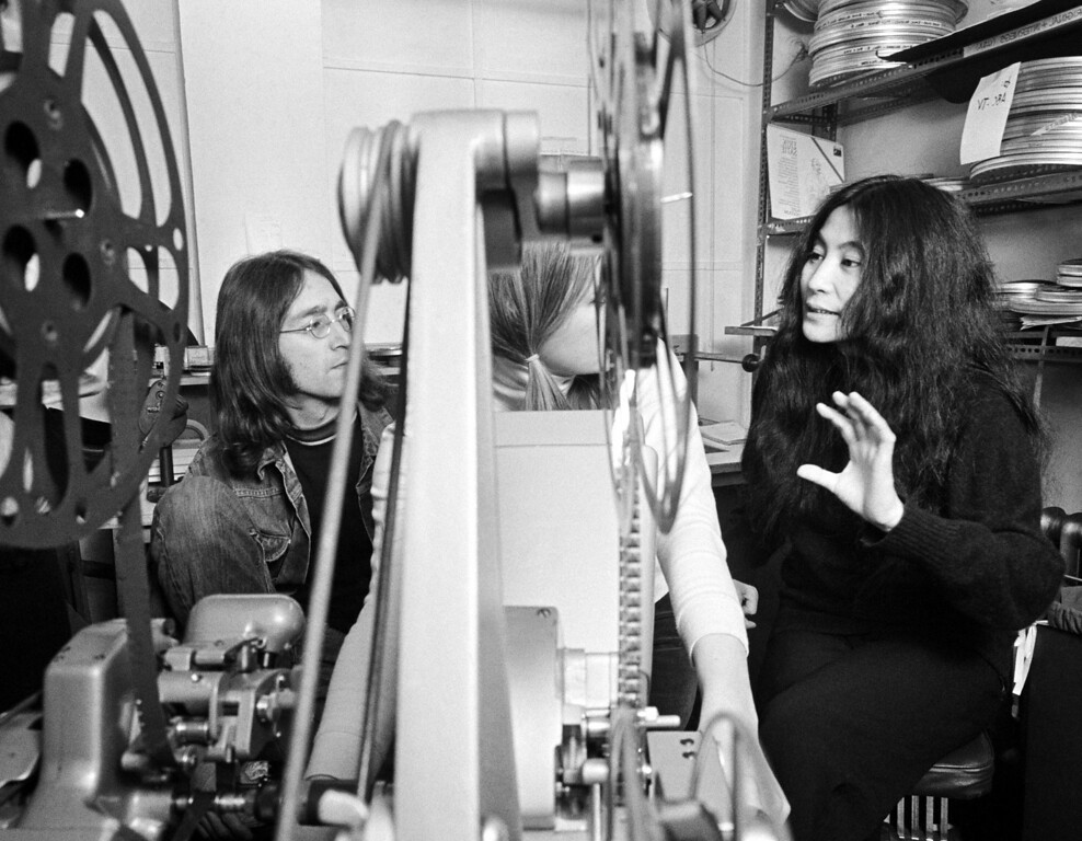 ". Beatle John Lennon, left, and his friend Japanese actress Yoko Ono go through the editing of the film ""Rape\"" together with an editor, partly obscured by the viewer Reel, in London, England, on Feb. 5, 1969. (AP Photo)"