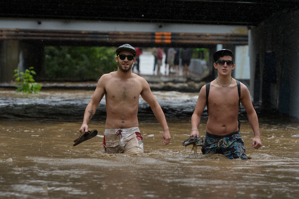 . BOULDER, CO. - SEPTEMBER12:  University of Colorado students (l-r) Ian Harris and Cody Hondorf attempt to cross a flooded underpass along Boulder Creek in Boulder, CO September 12, 2013. Record-breaking rain turned normally quiet creeks into raging, brown torrents that swept through Boulder on Thursday, flooding homes, swamping cars and closing roads and schools. (Photo By Craig F. Walker / The Denver Post)