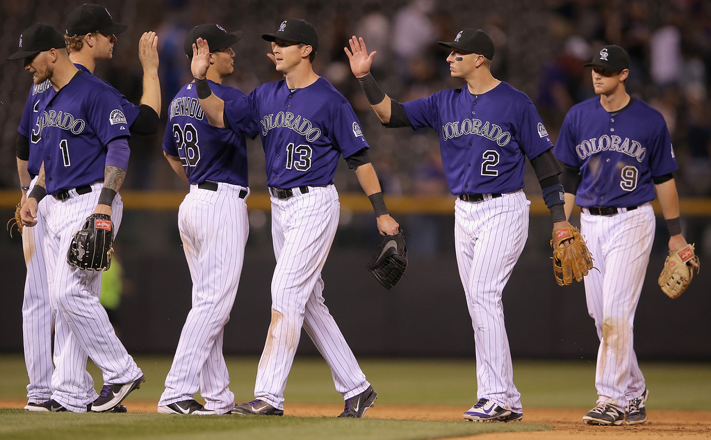 . Brandon Barnes #1, Justin Morneau #33, Drew Stubbs #13, Troy Tulowitzki #2 and DJ LeMahieu #9 of the Colorado Rockies celebrate their 8-2 victroy over the Texas Rangers during Interleague play at Coors Field on May 5, 2014 in Denver, Colorado.  (Photo by Doug Pensinger/Getty Images)