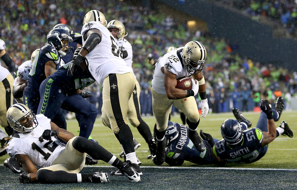 . SEATTLE, WA - JANUARY 11:  Running back Mark Ingram #22 of the New Orleans Saints scores on a two-point conversion in the fourth quarter against the Seattle Seahawks during the NFC Divisional Playoff Game at CenturyLink Field on January 11, 2014 in Seattle, Washington.  (Photo by Jeff Gross/Getty Images)