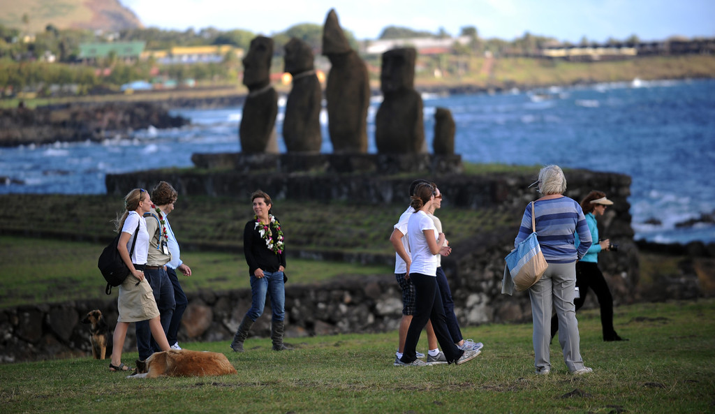 . A group of tourists visit Moais (background) -- stone statues of the Rapa Nui culture -- on Easter Island, 3700 km off the Chilean coast in the Pacific Ocean, on July 9, 2010. MARTIN BERNETTI/AFP/Getty Images