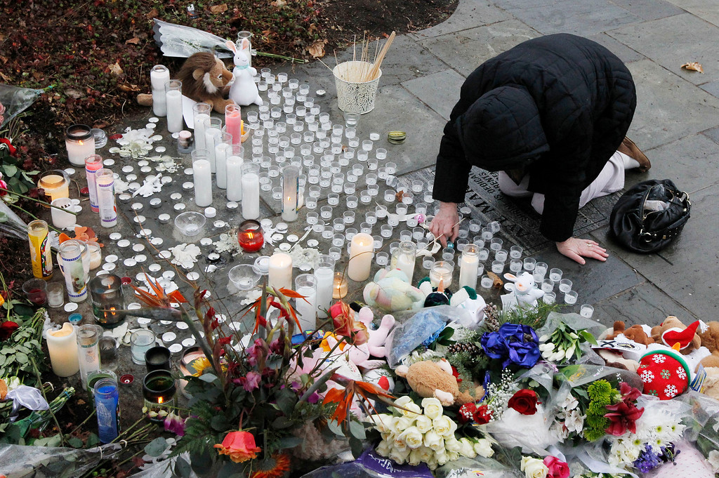 . A woman pays respects at a memorial outside of St. Rose of Lima Roman Catholic Church, Sunday, Dec. 16, 2012, in Newtown, Conn. On Friday, a gunman allegedly killed his mother at their home and then opened fire inside the Sandy Hook Elementary School in Newtown, killing 26 people, including 20 children. (AP Photo/Julio Cortez)