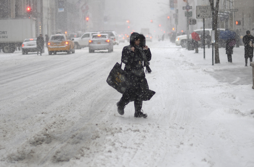 . A woman crosses 5th Avenue in the snow as New Yorkers get hit with a  winter storm in the Northeast January 21, 2014  that could bring up to a foot (30 cm) of snow in the city.  AFP PHOTO / TIMOTHY A. CLARY/AFP/Getty Images