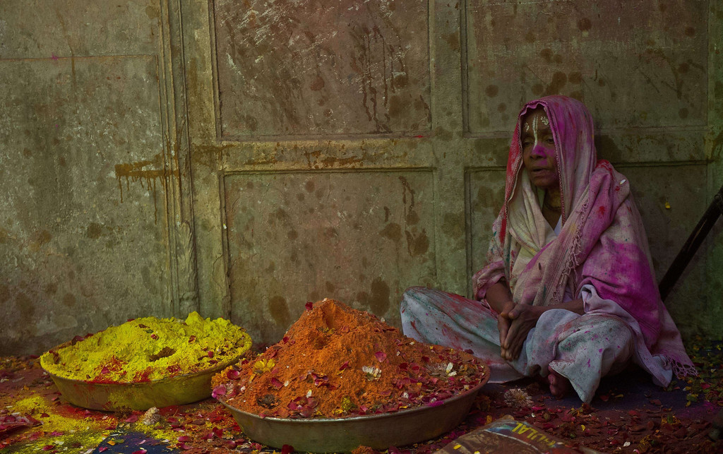 . An Indian widow prays while sitting next to trays of gulal (colored powder) during Holi celebrations in Vrindavan on March 14, 2014.  AFP PHOTO/Prakash SINGH/AFP/Getty Images