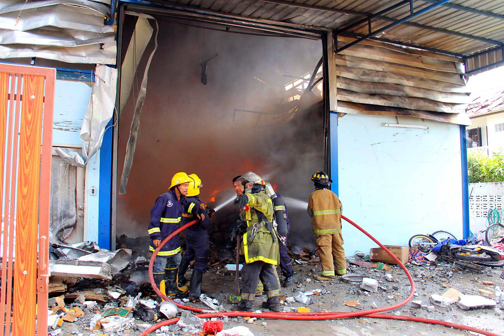 . Thai firemen fight the blaze after an explosion at a scrap shop in Bangkok, Thailand, Wednesday, April 2, 2014.  (AP Photo)