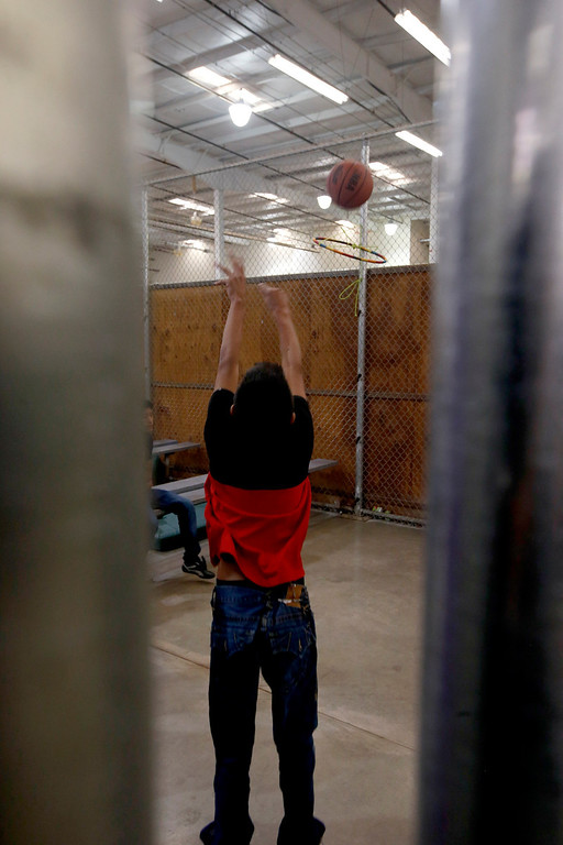 . A young boy shoots the basketball at a makeshift hoop in a holding cell where hundreds of mostly Central American immigrant children are being processed and held at the U.S. Customs and Border Protection Nogales Placement Center on Wednesday, June 18, 2014, in Nogales, Ariz.   (AP Photo/Ross D. Franklin, Pool)
