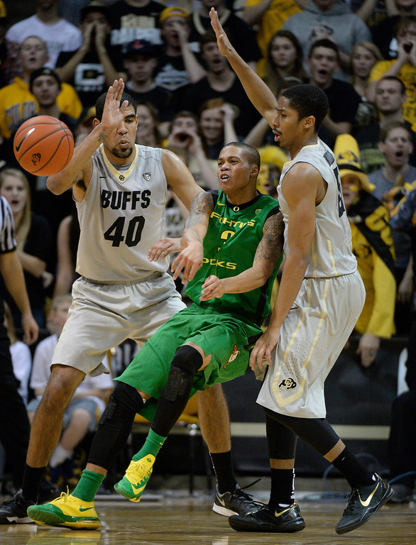 . Oregon Ducks guard Joseph Young (3) throws the ball back as he gets double teamed by Colorado Buffaloes forward Josh Scott (40) and Colorado Buffaloes guard Spencer Dinwiddie (25) during the second half January 5, 2014 at Coors Events Center. (Photo by John Leyba/The Denver Post)