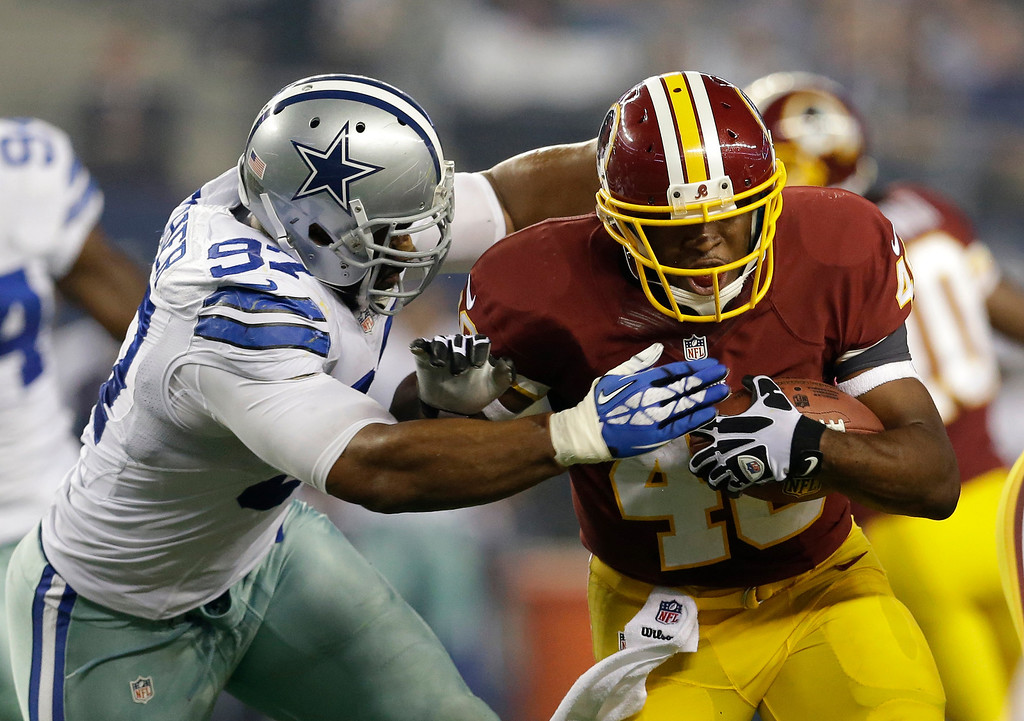 . Dallas Cowboys defensive end DeMarcus Ware (94) chases down Washington Redskins running back Alfred Morris (46) in the first half of an NFL football game, Sunday, Oct. 13, 2013, in Arlington, Texas. (AP Photo/LM Otero)
