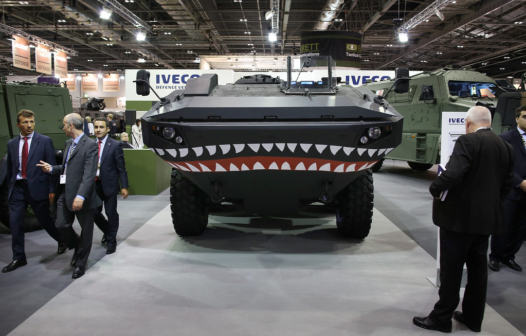 . Visitors walk past military vehicles displayed at the Defence and Security Exhibition on September 10, 2013 in London, England.  (Photo by Peter Macdiarmid/Getty Images)