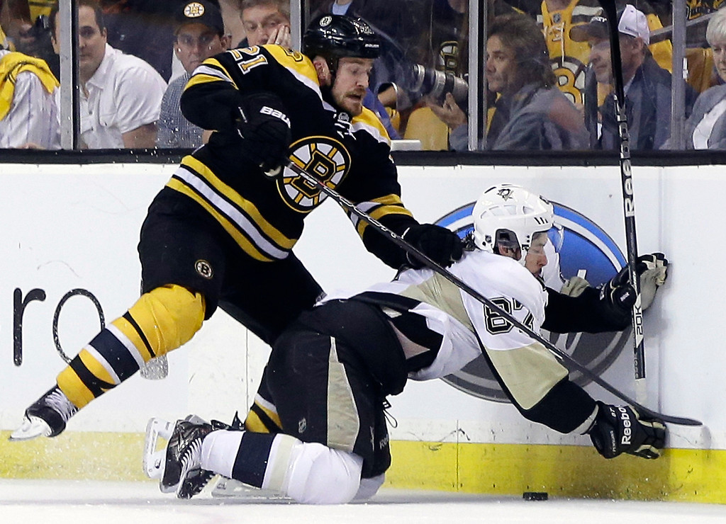 . Boston Bruins defenseman Andrew Ference (21) grapples for the puck against Pittsburgh Penguins center Sidney Crosby (87) during the second period in Game 3 of the Eastern Conference finals in the NHL hockey Stanley Cup playoffs, in Boston on Wednesday, June 5, 2013. (AP Photo/Elise Amendola)