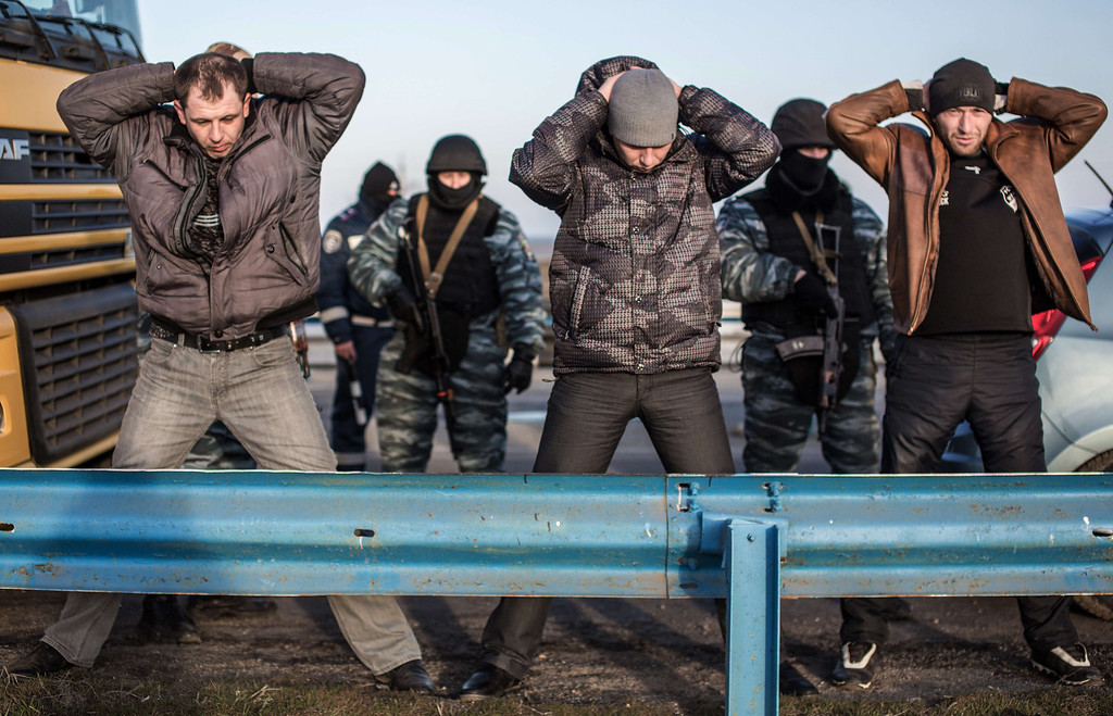 . Men hold their hands up on their heads as they are searched by pro-Russian servicemen at Chongar checkpoint blocking the entrance to Crimea on March 10, 2014. Russia vowed on March 10 to unveil its own solution to the Ukrainian crisis that would run counter to US efforts and would appear to leave room for Crimea to switch over to Kremlin rule. The unexpected announcement came as Ukraine\'s new pro-European leaders raced to rally Western support in the face of the seizure by Kremlin-backed forces of the strategic Black Sea peninsula and plans to hold a Sunday referendum on switching Crimea\'s allegiance from Kiev to Moscow. ALISA BOROVIKOVA/AFP/Getty Images