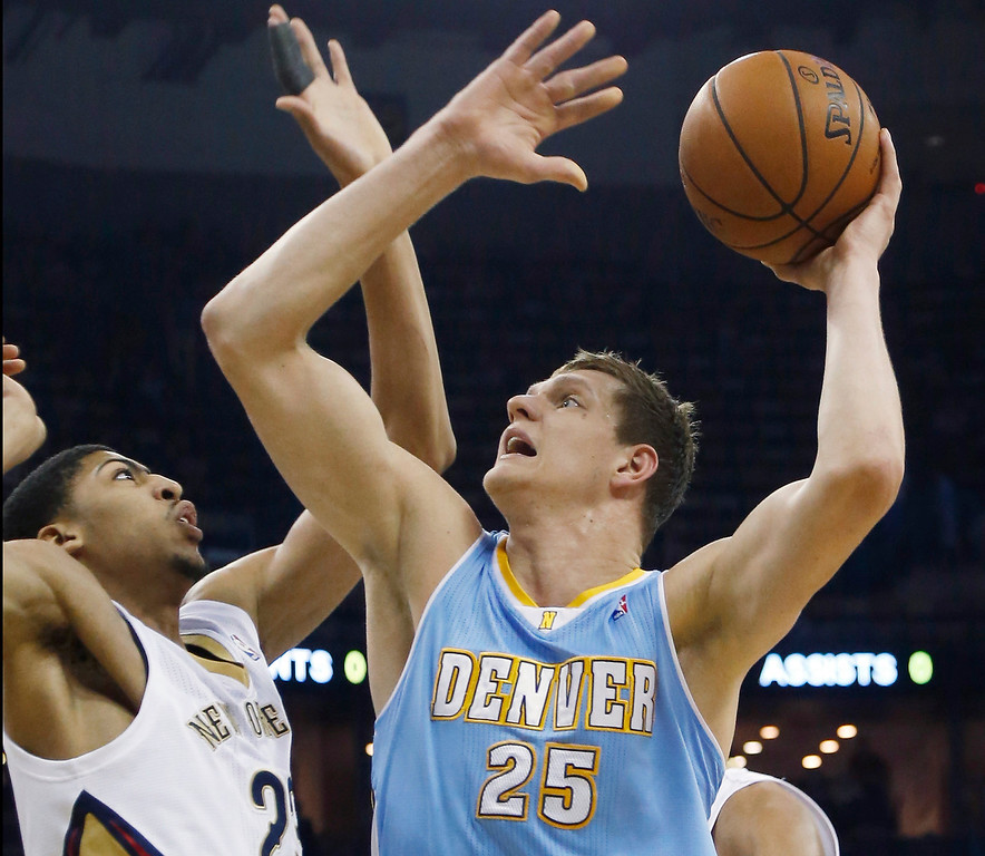 . Denver Nuggets center Timofey Mozgov (25) shoots over New Orleans Pelicans power forward Anthony Davis (23) in the first half of an NBA basketball game in New Orleans, Sunday, March 9, 2014. (AP Photo/Bill Haber)