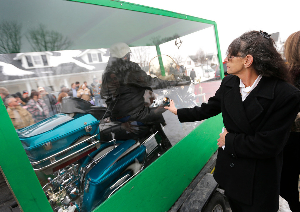 . Theresa Adams, daughter of Bill Standley, says goodbye to her dad whose body is secured to his 1967 Harley Davidson inside a plexiglass box during his funeral service in Mechanicsburg, Ohio on Friday, Jan. 31, 2014.   (AP Photo/Columbus Dispatch, Jonathan Quilter)