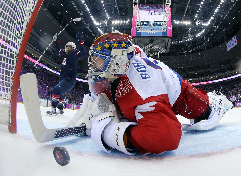 . USA forward Phil Kessel reacts as Russia goaltender Sergei Bobrovski can\'t stop a goal by USA defenseman Cam Fowler during the second period of a men\'s ice hockey game at the 2014 Winter Olympics, Saturday, Feb. 15, 2014, in Sochi, Russia. (AP Photo/Bruce Bennett, Pool)