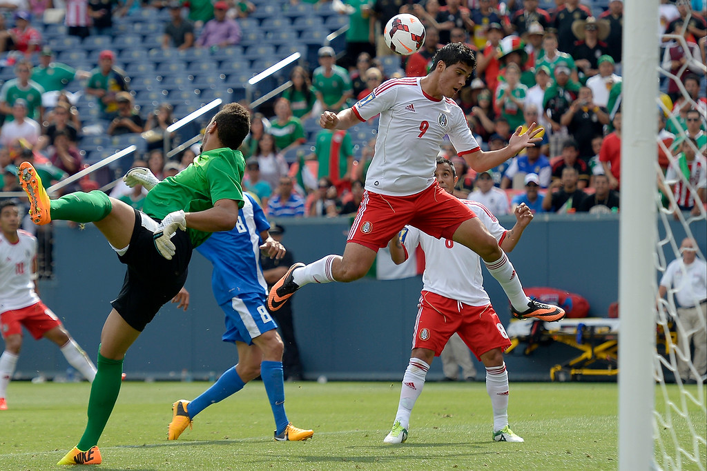 . Raul Jiminez #9 of Mexico tries to redirect a kick past goaltender Kevin Olimpa #23 of Martinique during the first half of the CONCACAF Gold Cup soccer game July 14, 2013 at Sports Authority Field at Mile High. (Photo By John Leyba/The Denver Post)