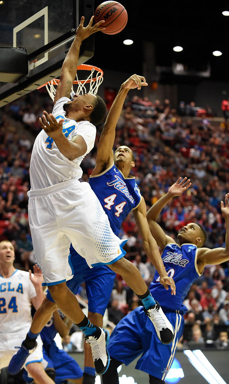 . UCLA guard Norman Powell, left, tries to get a shot around the backboard as Tulsa forward Brandon Swannegan (44) and guard James Woodard, right, defend during the second half of a second-round game in the NCAA men\'s college basketball tournament Friday, March 21, 2014, in San Diego. (AP Photo/Denis Poroy)