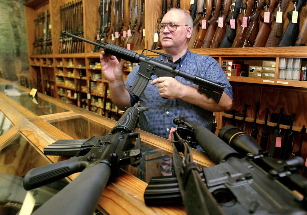 . Gun dealer Tom Mannewitz displays several United States-made assault-style rifles inside his Dallas, Texas gun shop, September 13, 2004.  REUTERS/Jeff Mitchell