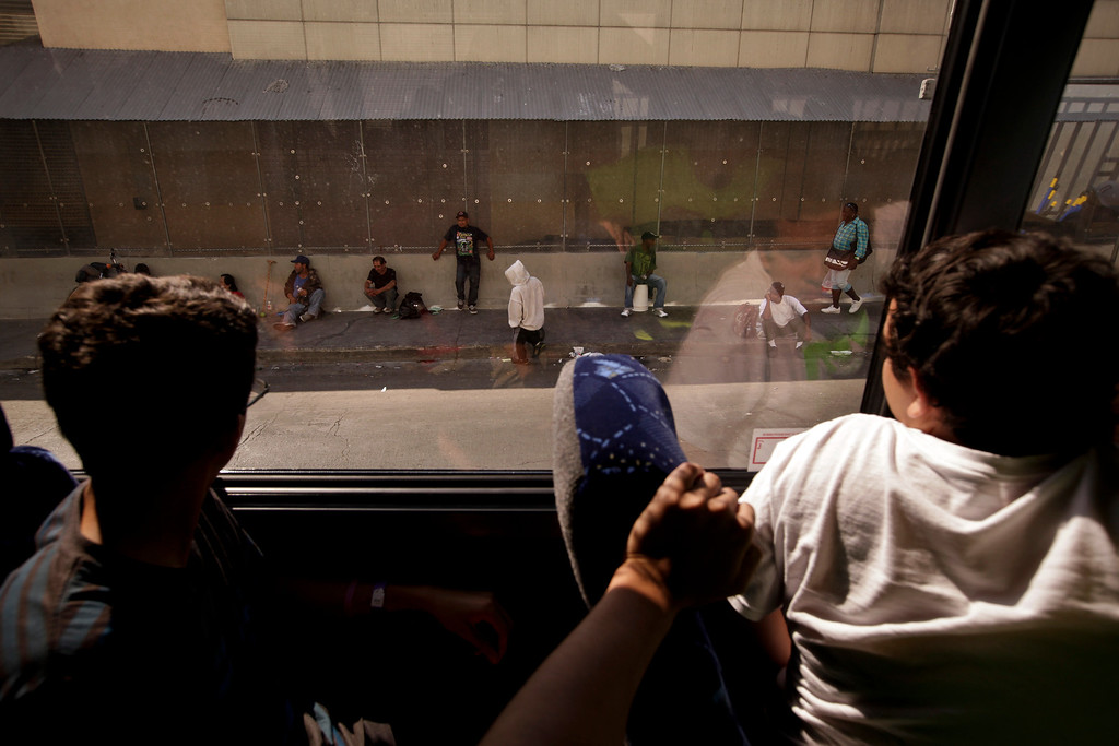 . Young volunteers from the Dream Center, a Christian church mission, look at homeless people from inside their bus in the Skid Row area of Los Angeles on Thursday, July 18, 2013. (AP Photo/Jae C. Hong)