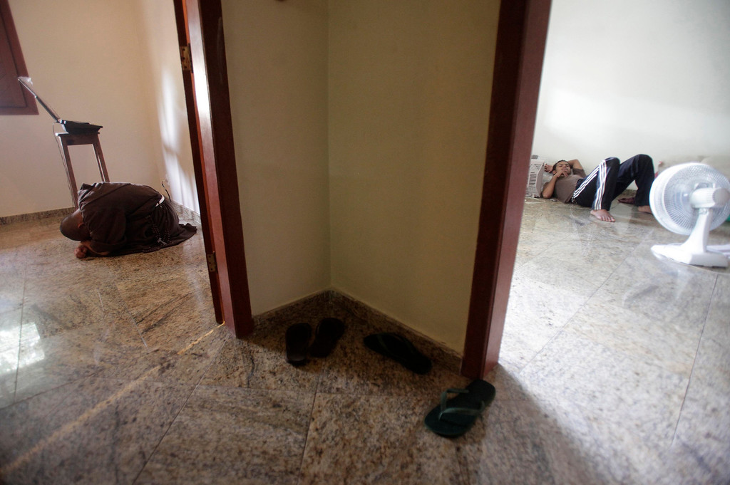. Brother Placido (L) of the Franciscan fraternity O Caminho, prays at the chapel of the fraternity\'s house as apprentice Leanderson (R) rests in another room in the Campo Grande neighbourhood of Rio de Janeiro April 2, 2013. O Caminho (The Way), are a group of Franciscan monks and nuns who help the homeless on the streets of Rio de Janeiro. They consider the election of Pope Francis, the first pontiff to take the name of St Francis of Assisi, to be a confirmation of their beliefs in poverty and simplicity. In July, Pope Francis will visit Rio de Janeiro in his first international trip since assuming the papacy. Picture taken April 2, 2013. REUTERS/Ricardo Moraes