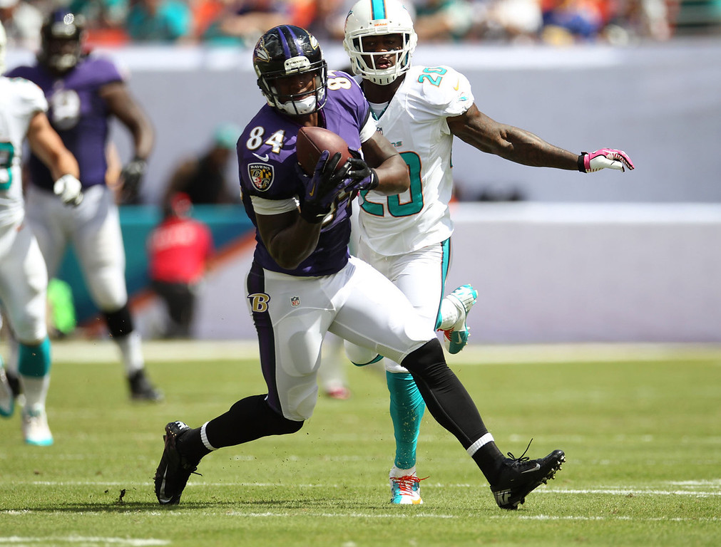 . Tight end Ed Dickson #84 of the Baltimore Ravens makes a catch against Reshad Jones #20 of the Miami Dolphins at Sun Life Stadium on October 6, 2013 in Miami Gardens, Florida.  (Photo by Marc Serota/Getty Images)