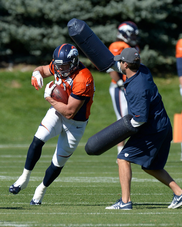 . Denver Broncos tight end Joel Dreessen (81) catches a pass during practice as he gets hit with pads October 2, 2013 at Dove Valley. (Photo by John Leyba/The Denver Post)
