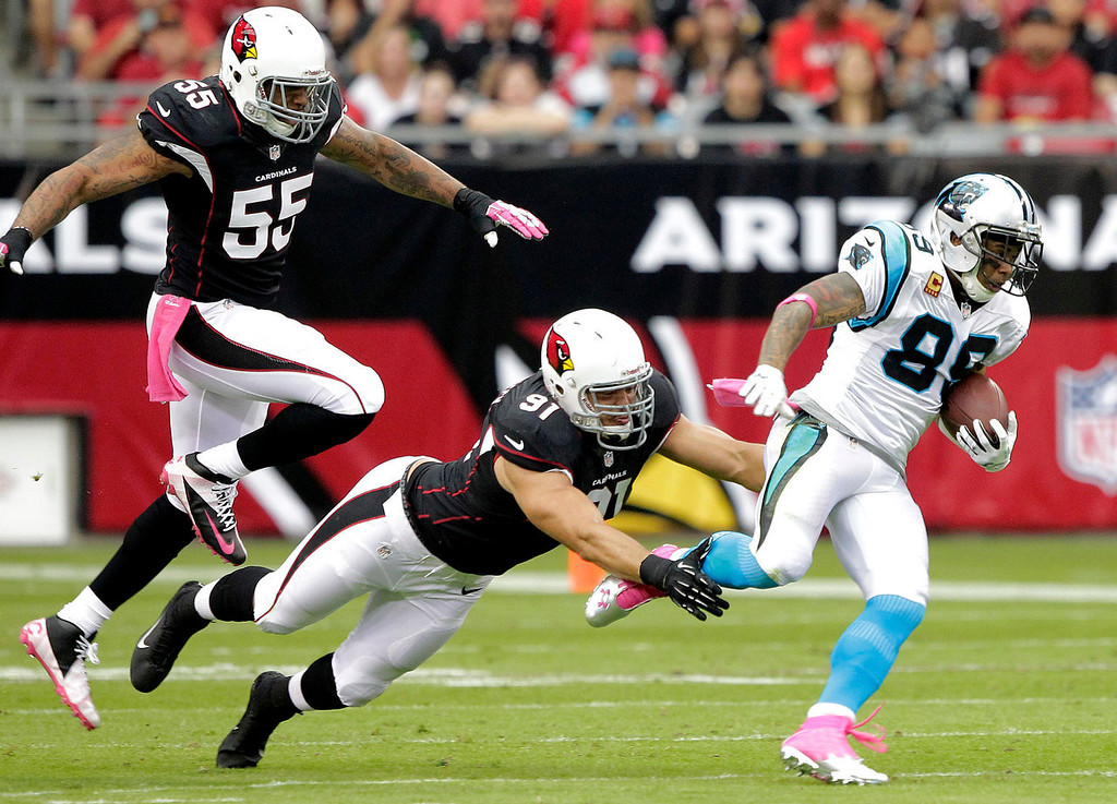 . Carolina Panthers wide receiver Steve Smith (89) escapes the reach of Arizona Cardinals defensive end Matt Shaughnessy (91) and John Abraham during the first half of a NFL football game, Sunday, Oct. 6, 2013, in Glendale, Ariz. (AP Photo/Rick Scuteri)