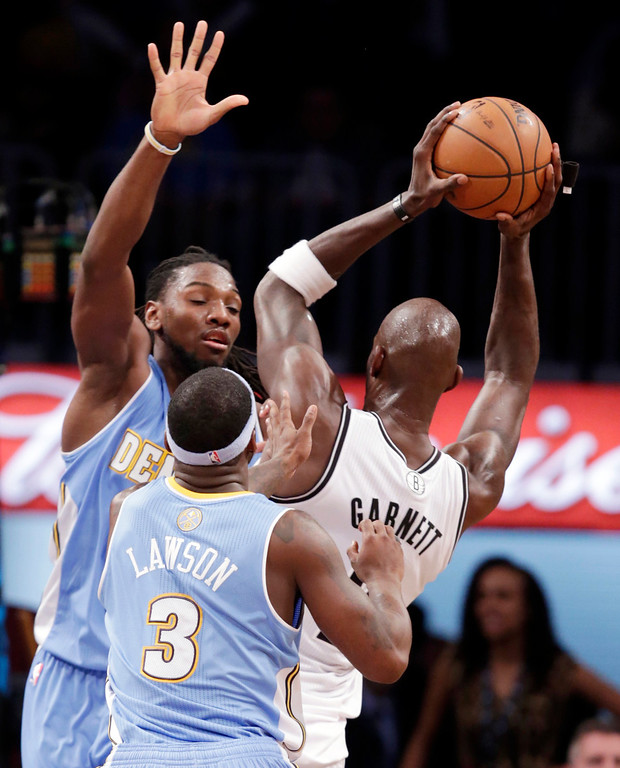 . Denver Nuggets forward Kenneth Faried, left, and Denver Nuggets point guard Ty Lawson (3) defend Brooklyn Nets forward Kevin Garnett (2) in the second half of an NBA basketball game Tuesday, Dec. 3, 2013, in New York. The Nuggets won 111-87. (AP Photo/Kathy Willens)