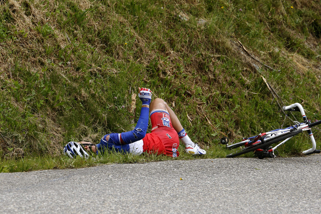 . France\'s Arthur Vichot lies on the grass after falling during the 204.5 km nineteenth stage of the 100th edition of the Tour de France cycling race on July 19, 2013 between Bourg-d\'Oisans and Le Grand-Bornand, French Alps.  AFP PHOTO / JOEL SAGET/AFP/Getty Images